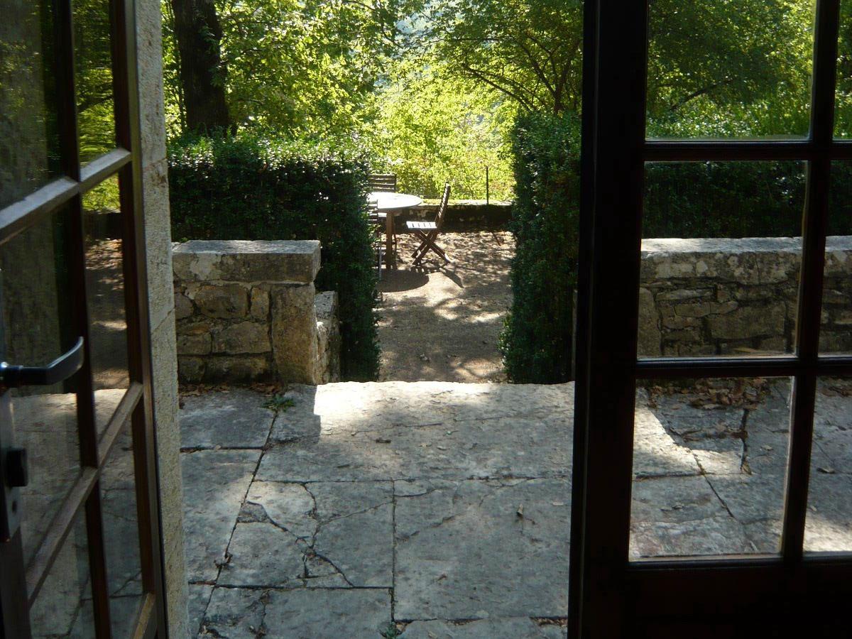La cour intérieure, petite terrasse en pierre et grande terrasse ombragée